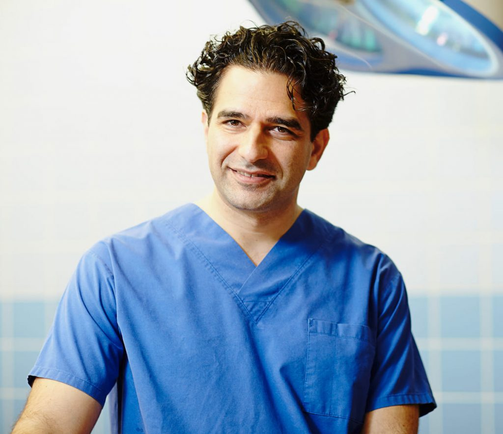 Behandlung - Dr. Hambarchian in blauem Chirurgenkittel im OP-Saal